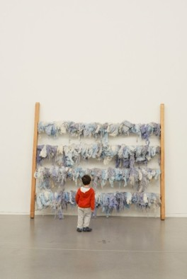 child in red in front of artwork